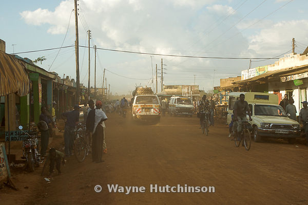 Dusty street scene with cars and people on bicyles , Mumias , Kenya Africa