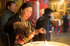 A woman pouring liquid yak butter into candles at Dreprung Monastery in Lhasa, Tibet.