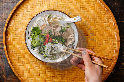 Pho Bo vietnamese Soup with beef and chopsticks in male hand copy space