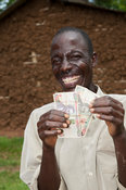 Happy Kenyan farmer holding banknotes earned by selling milk from his cow. Kenya.