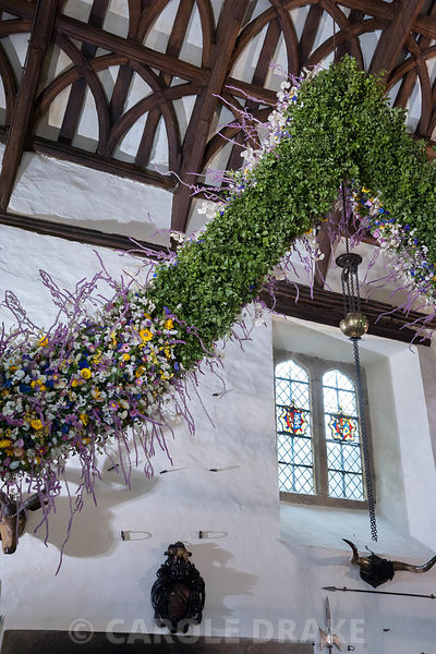 Christmas garland midway through construction revealing its inner framework of pittosporum foliage into which the flowers and grasses are inserted. Cotehele, St Dominick, nr Saltash, Cornwall, UK