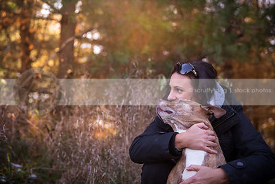 beautiful stock image of senior dog being hugged by owner by backlit forest