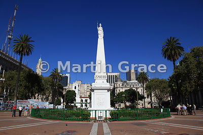 White marble statue of the May Pyramid (1811) shining in sun and clear blue sky, Plaza de Mayo, Buenos Aires, Argentina