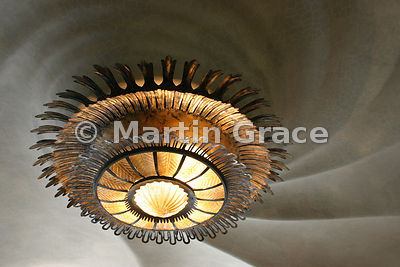Ceiling of Gaudi-designed Casa Batllo apartment in Barcelona showing whirlpool smooth plaster ceiling & bronze sun-ray light