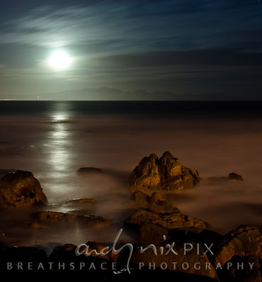 Night shot of moon rising over mountains above Gordon's Bay with path of moonlight across False Bay, orange light on rocks and blured waves in foreground