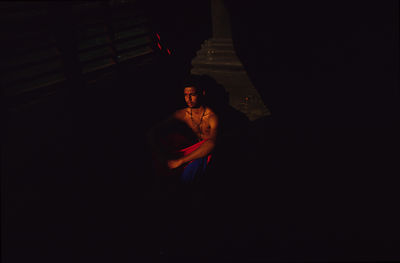 India - Kerala - A boy in the shadows outside the Koothabalam
