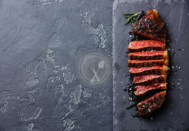 Sliced medium rare grilled Striploin steak on slate board copy space