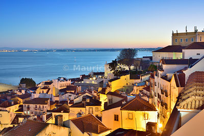Alfama district at twilight facing the Tagus river. Lisbon, Portugal