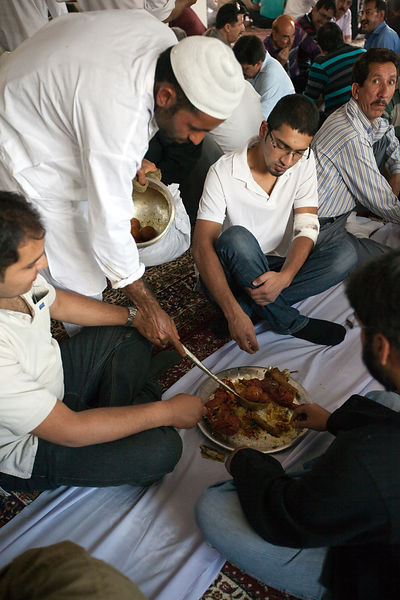 India - Srinagar - Male guests at a wedding party are served and eat a traditional Wazwan meal seated in groups of four around a communal plate called a Trami