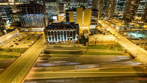 Bird's Eye: Medium Shot - Panning Upwards From the Busy Kennedy Expressway to a Chicago Skyline Under Brilliant Moonlight