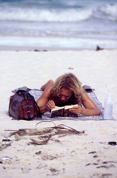 A hippy traveller reads a book on the beach