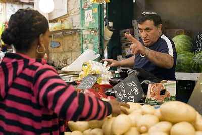 Israel - Jerusalem - A man buys vegetable on a stall in the Mahane Yahuda Market