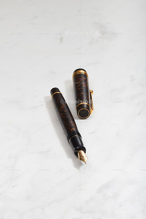 Fountain pen with side lid on white marble background