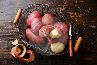 Raw potato in metal basket on wooden background