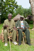 Pair of village elders sitting on home made chairs on village green, Kenya.