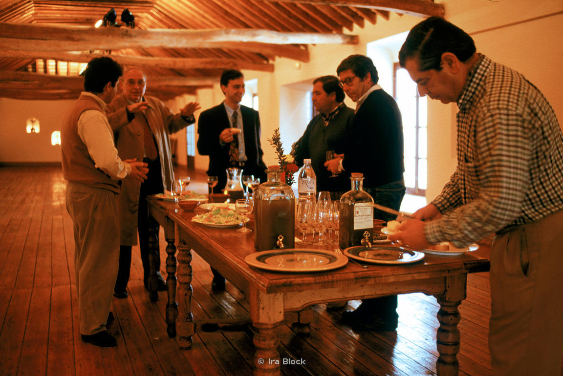 Business men gather for wine and Spanish fingerfood.