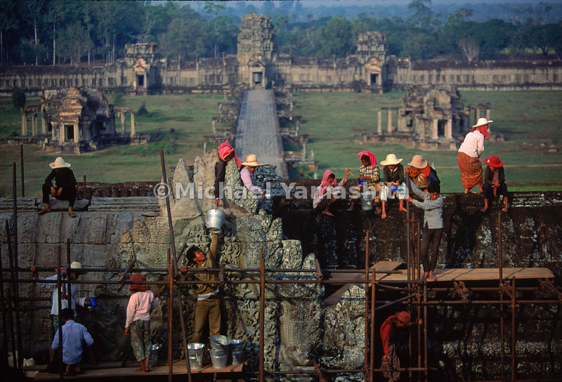Workers, reclaiming the great temple from the ravages of time and war, scour the front facade of Angkor Wat, as part of a United Nations restoration effort begun in 1986. Cambodia.