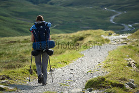 A woman hiker walking along a long stone path with a large backpack in the Lake District.