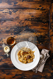 Risotto with porcini mushroom on plate on wood table background copy space