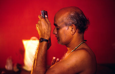 India - Kerala - Professor Balasubramanian, a senior teacher of Kathakali prays before starting to apply his make up