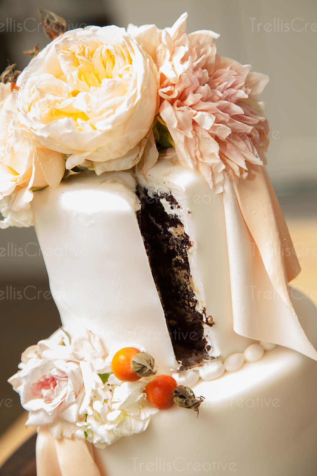 Close up of the wedding cake with delicate white and blush flowers decorations