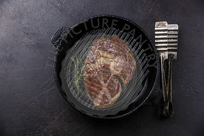 Grilled Rib eye steak and tongs on grill pan on dark background