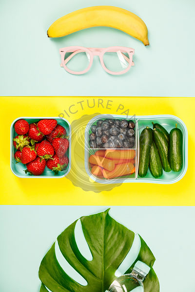 Creative flat lay with glasses, healthy lunch and monstera leaf on pastel colors background