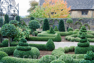Clipped box and yew in the Parterre Garden punctuated by standard laurels and a gazebo and gates by Richard Overs. Bourton House, Bourton-on-the-Hill, Moreton-in-Marsh, Glos, UK