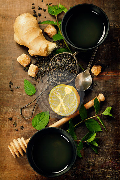 Cups of tea, lemon, ginger and mint on a wooden background