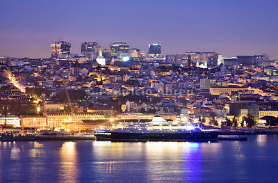 Lisbon at dusk and a cruise ship on the Tagus river. Portugal