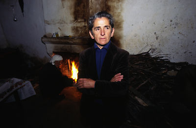 Albania - Thethi - Pashke Sokol Ndocaj stands by a pile of firewood as her uncle lights a fire in her house.