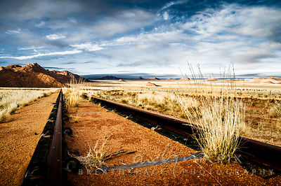 A low angle view of a an old rusted railway receding into the desert in the distance, tufts of dry veld grass growing between the tracks, hills in the distance