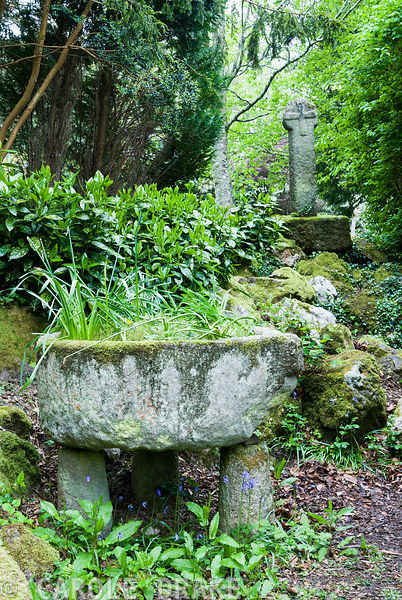 The Cornish Cross with stone apple press in foreground. Enys Gardens, St Gluvias, Penryn, Cornwall, UK
