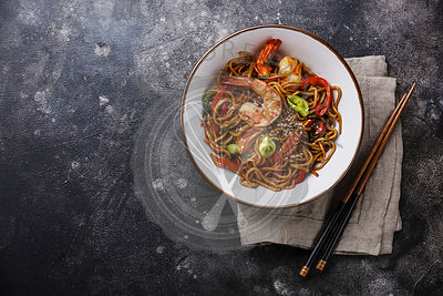 Udon noodles stir-fried with Tiger shrimps and vegetable in bowl on dark background copy space