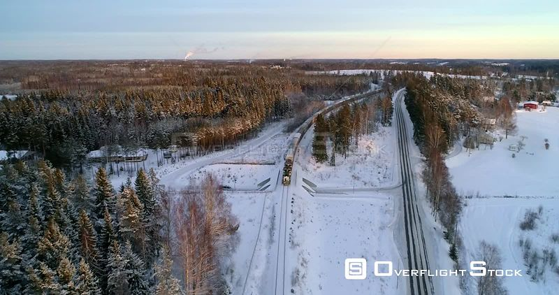 Train on a Winter Countryside, Aerial, Reverse, Drone Shot, Following a Cargo Locomotive, at Sunset, in Scandinavian Nature, on a Sunny, Autumn Evening, in Uusimaa, Finland