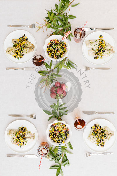 A summery (happy & bright) tablesetting with a portion of Baked Lime and Olive oil tilapia with black bean salsa served on each plate.