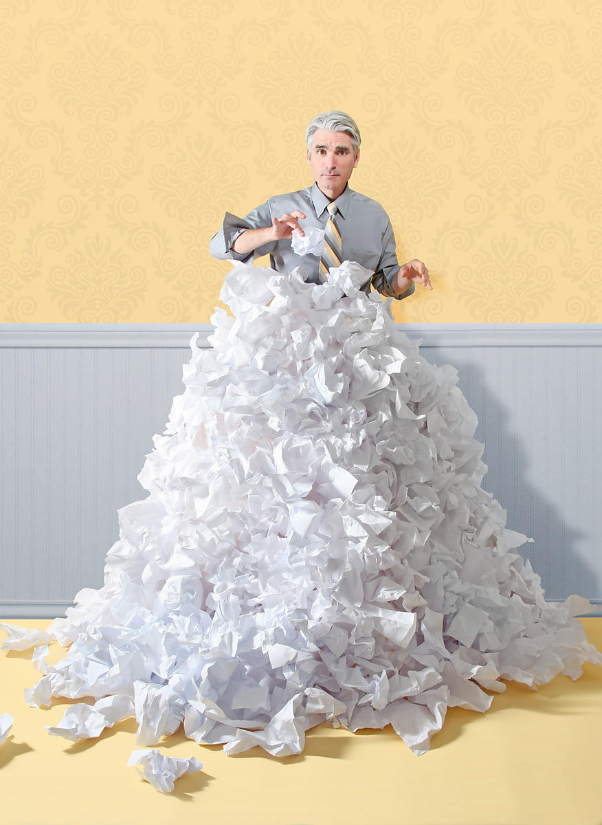 Business man trapped in large pile of crumpled paper