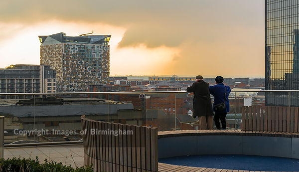 Visitors at The New Library of Birmingham, watching the sun set.