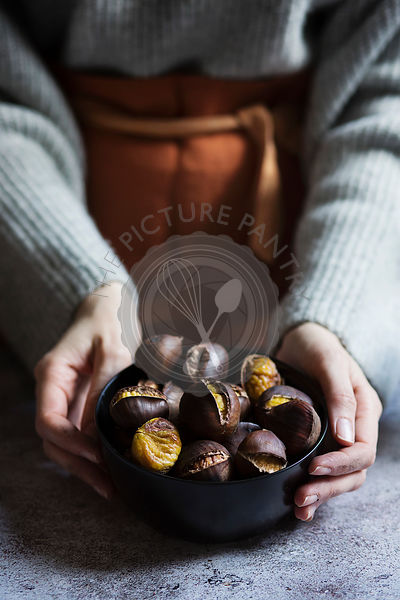 Woman holding roasted chestnuts in a bowl