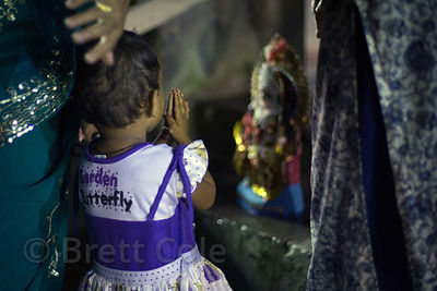 A toddler girl prays to her family's idol of the goddess Durga along the Hooghly River during the Durga Puja festival, Babughat, Kolkata, India