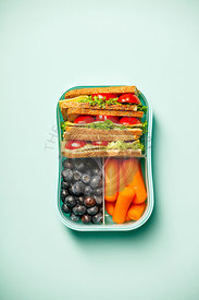 Creative flat lay with healthy lunch in blue container on pastel blue background
