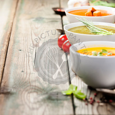 Variety of cream soups - tomato, broccoli and pumpkin soups over wood background. Copy space