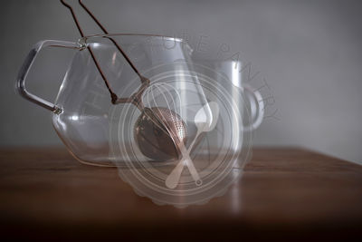 Glass tea set with geometric tea pot, tea cup and copper diffuser on a butcher block kitchen counter with soft morning light.