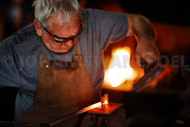 Blacksmith bending red hot iron