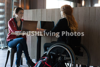 Young woman using a wheelchair studying in a cafe with her friend