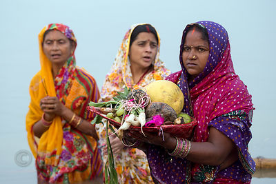 Women make offerings on the Ganges River during Chhath Puja, Varanasi, India. Chhath Puja is a devotion to the Sun God Surya in which people gather at sunset and then on the following sunrise and offer prayers.