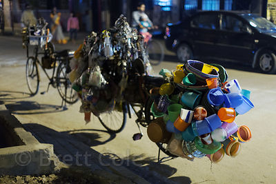 A bicycle laden with plastic goods serves as a mobile storefront, Lake Gardens, Kolkata, India.