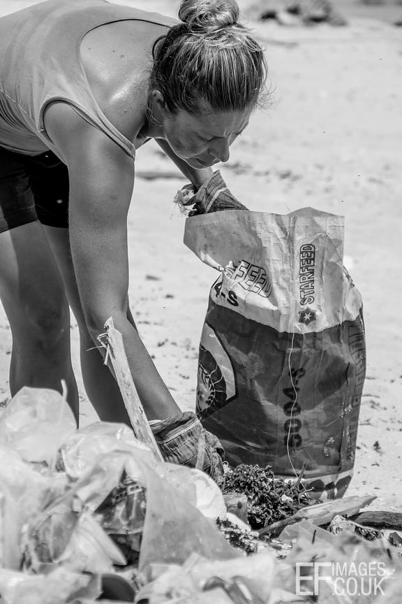 Woman Sorting Plastic Trash Washed Up On A Beach