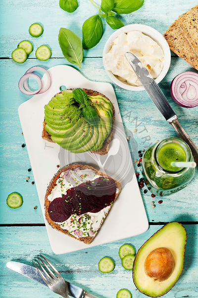 Healthy Vegetarian Sandwiches (with Avocado, Tomato,  Cucumber, Onion, Beetroot, Cream Cheese, Herbs and Spices) on blue rustic background