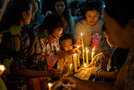 People holding candles at Wat Yan Nawa during Magha Puja, an important Buddhist festival celebrated on the full moon day in Bangkok, Thailand.